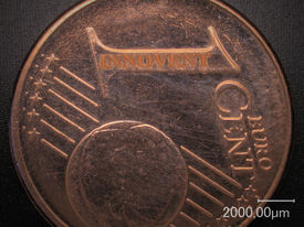 "For demonstration of the spatial resolution: Laser engraving the lettering ""INNOVENT"" on a 1 €-cent coin is shown."