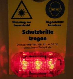 The Picture shows a warning lamp at the entrance to the laser laboratory, which warns of the laser irradiation and requests to wear protective glasses.