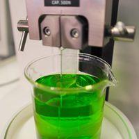 Es erfolgt eine Tauchbeschichtung einer Glasprobe in einer grünen Flüssigkeit.