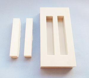 Die Abbildung zeigt zwei gegossene Formkörper neben der Gießform.