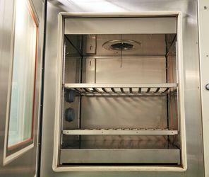 Abbildung eines Klimaschranks vom Typ KPK200 mit geöffneter Tür. Der Innenraum ist aus Edelstahl und es sind zwei Metalleinschübe montiert. An der Decke der Kammer ist die Lüftungsöffnung zu sehen. Auf der linken Seite befinden sich zwei durch Kappen verschlossene Durchführungsöffnungen.