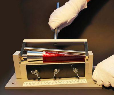 Gezeigt wird die Dornbiegeprüfung mit konischem Dorn an einen lackierten Aluplatte zur Ermittlung der Lackhaftfestigkeit.