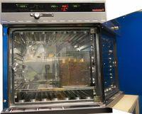 Diese Abbildung zeigt die Feuchtekammer HCP 108 mit Moderfäuletest. Die Kammertür ist geöffnet aber eine weitere Glastür verschließt noch den Probenraum. Im Probenraum steht eine mit Erde gefüllte Glaswanne, in der Holzproben stecken. Oberhalb des Probenraumes befindet sich das Steuerungsdisplay mit Anzeigen für die Temperatur, die Luftfeuchtigkeit und eine Zeitanzeige.