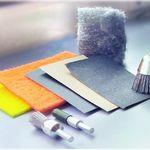 Abbildung von Schleifzubehör. Verschiedene Schleifpapiere, Schleifschwämme, Metallwatte und Schleifköpfe für Rotationsschleifer.