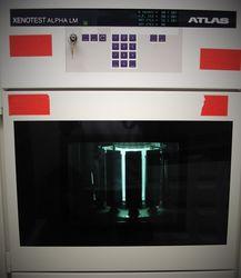 Die Abbildung zeigt den Xenotester Beta+. Die Testkammer ist in Betrieb und man sieht die Proben auf einen Probenkarusell um die hell erleuchtete Strahlungsquelle im Mittelpunkt fahren.