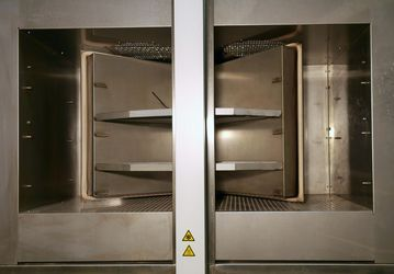 Picture of the temperature shock test chamber TSK 200 with opened doors and sample cabin in middle position is shown.