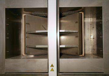 Die Abbildung zeigt eine Temperaturschockkammer TSK 200. Beide Kammern sind geöffnet. Der Fahrkorb befindet sich zwischen beiden Kammern in Mittelstellung. Im Fahrkorb sind zwei Blecheeinsätze montiert.