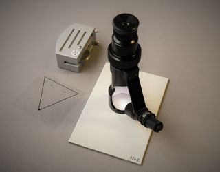 The picture presents the Buchholz hardness tester with a template and the hand-held microscope for the examination of the indentation pattern.