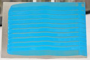 Die Abbildung zeigt einen Prüfkörper nach Lackauftrag mit einem Verlaufsrakel. Es ist ein blauer Lack in verschieden Schichtdicken streifenförmig aufgetragen. Das Prüfblech wurde aufrecht gestellt. Die Lackstreifen verlaufen dadurch horizontal. Wenn es zu einem Verlaufen kommt, dann bilden sich Farbnasen. Diese Farbnasen sind im Bild nicht zu sehen, daher ist die Prüfung bestanden.