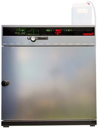 Die Abbildung zeigt die Feuchtekammer HCP 108. Man sieht einen quaderförmiges Gerät aus Edelstahl. Das Gerät hat eine große metallische Tür hinter der sich der Probenraum verbirgt. Oberhalb der Tür gibt es eine Anzeige, die die Temperatur und die Luftfeuchtigkeit anzeigt.