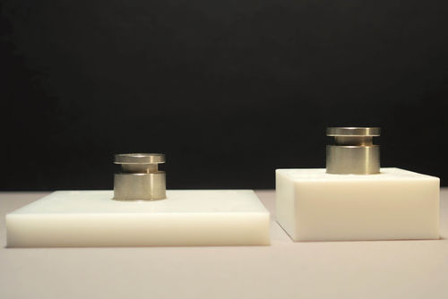 Dargestellt sind je ein Verbund von verklebten Stahlzylindern mit POM (links) und PTFE (rechts).