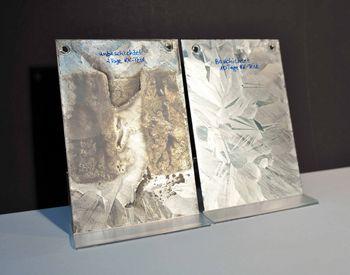 Dargestellt sind 2 feuerverzinkte Stahlbleche, die einen 10-tägigen Kondenswasser-Konstantklima-Tests (KK-Test) durchliefen. Das linke Bild zeigt sowohl Bereiche ohne (links) und mit Konservierung (rechts).