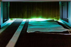 textile Gewebe beim Durchlauf der NIQ-Bestrahlungseinheit